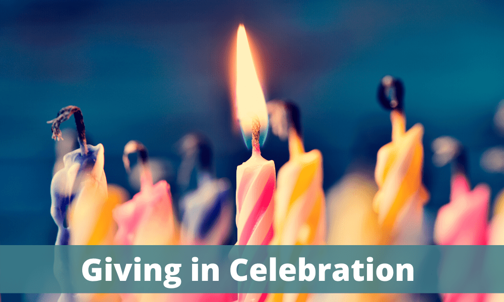 Giving in celebration - lit candles on a cake