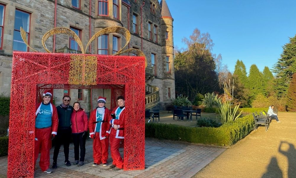 Team of 5 abseilers dressed in Santa costumes underneath a large gazebo that looks like a present as an event novelty, the background shows the side of Belfast Castle